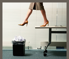 20223087(Businesswoman Stepping Off Table Into Wastebasket)